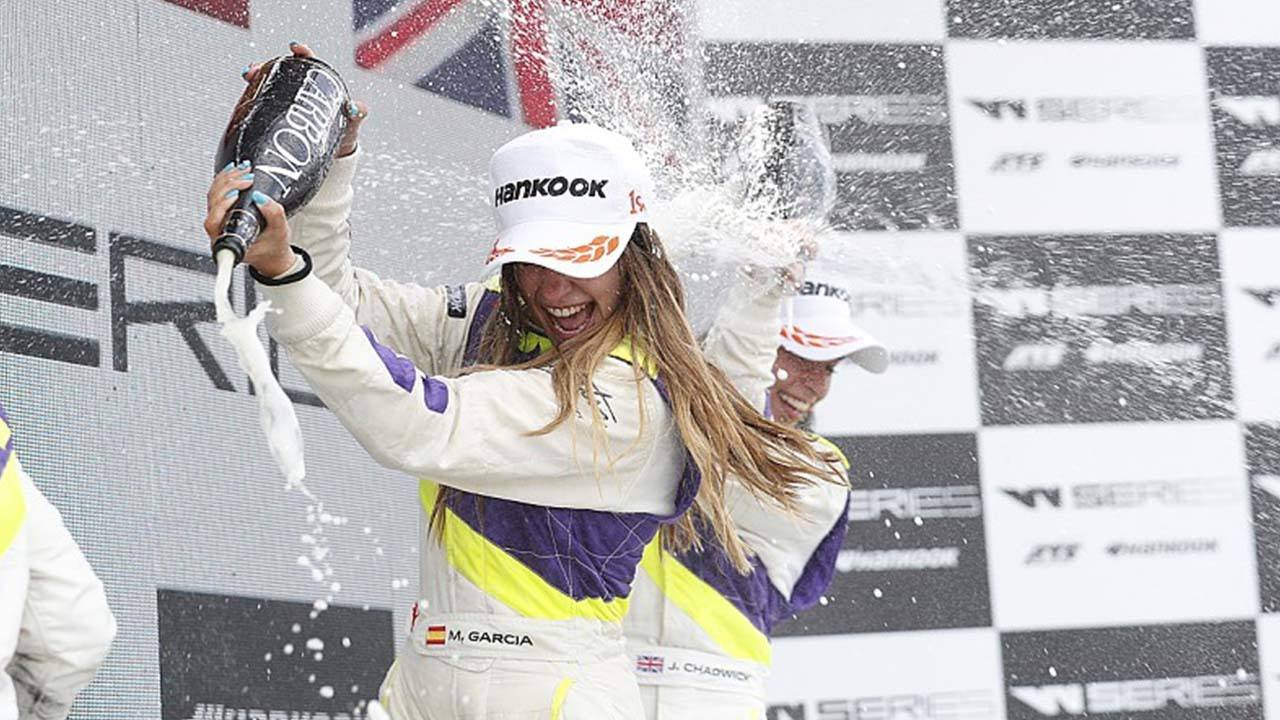 Two W Series drivers spray each other with champagne on the podium