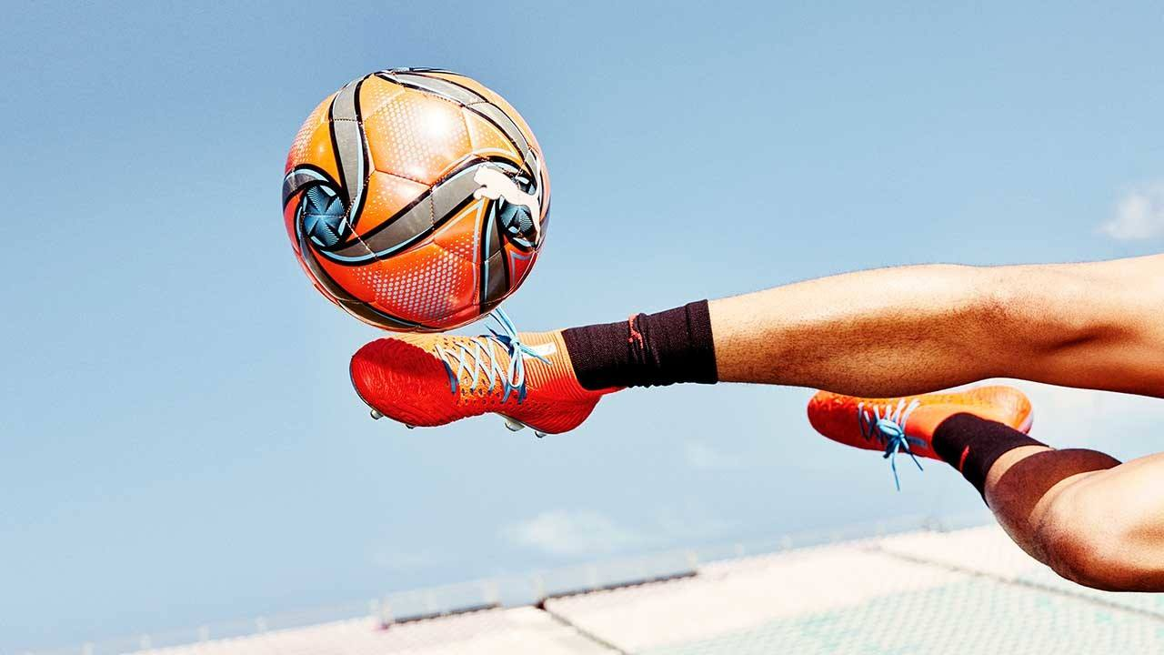 Close up of footballer kicking a branded ball in the latest boots