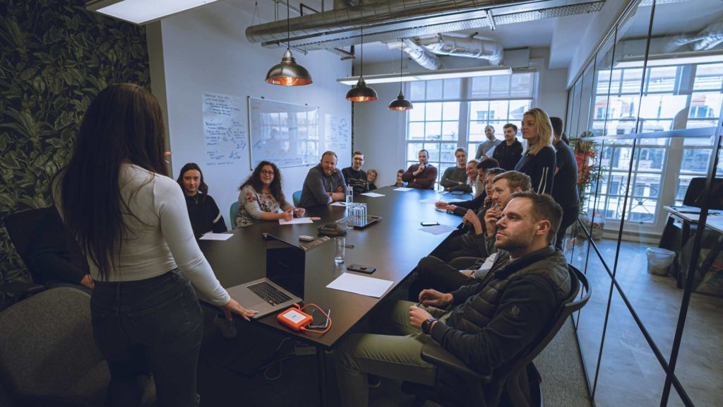 Maria presenting to a meeting room full of employees