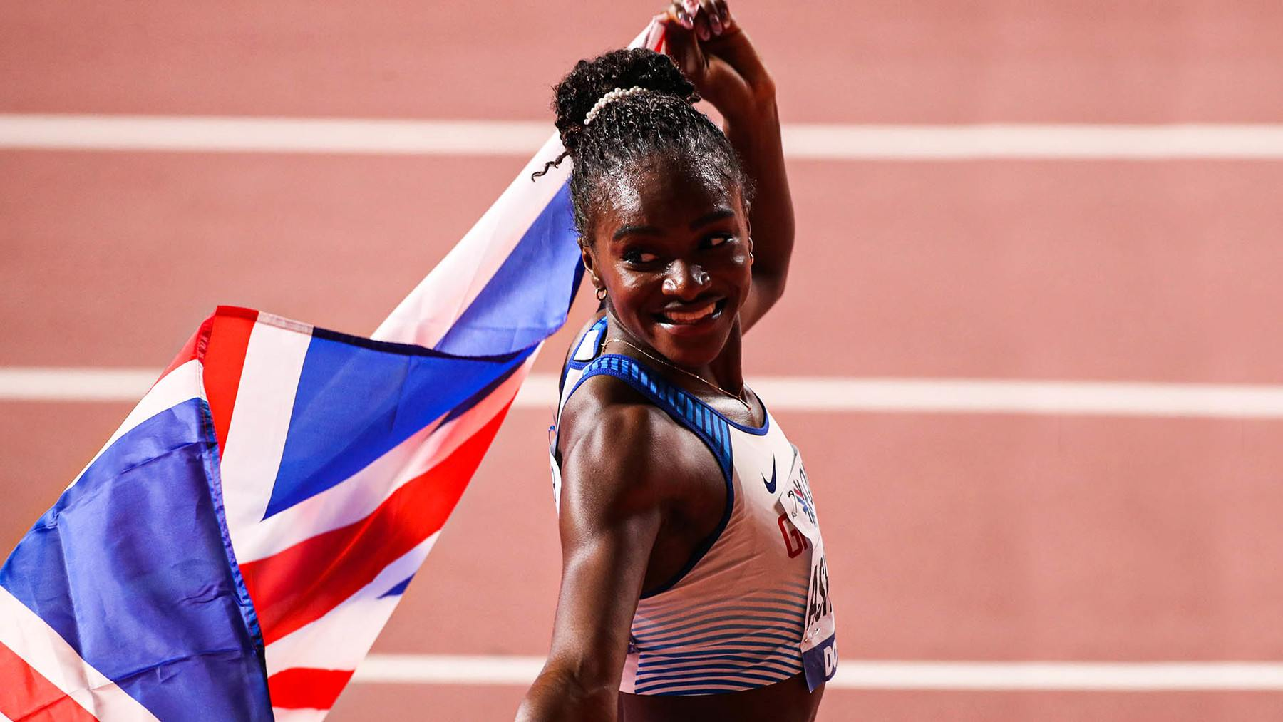 Dina Asher-Smith with a GB flag at Doha 2019